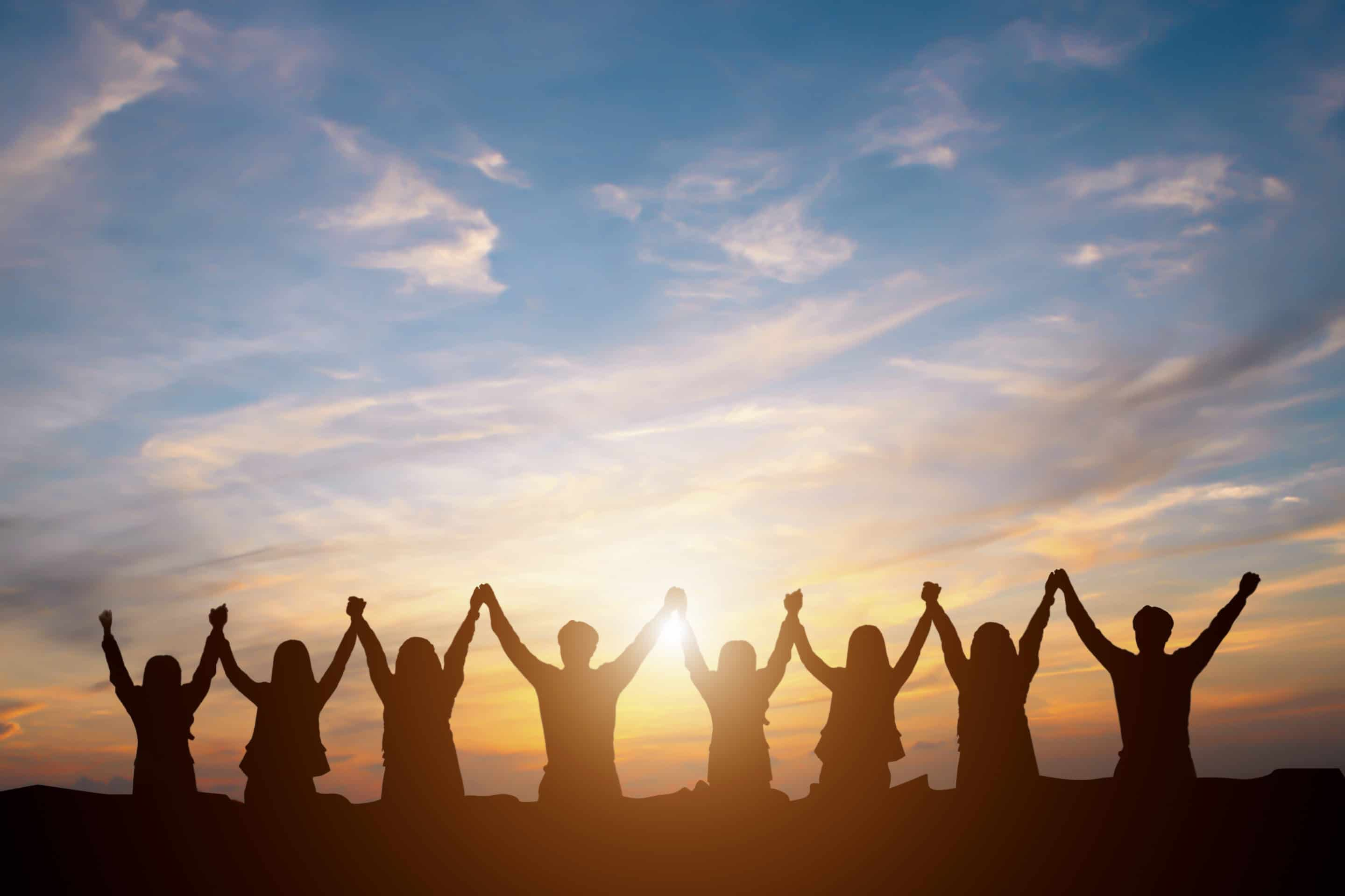 a team of people holding hands up in the air in celebration