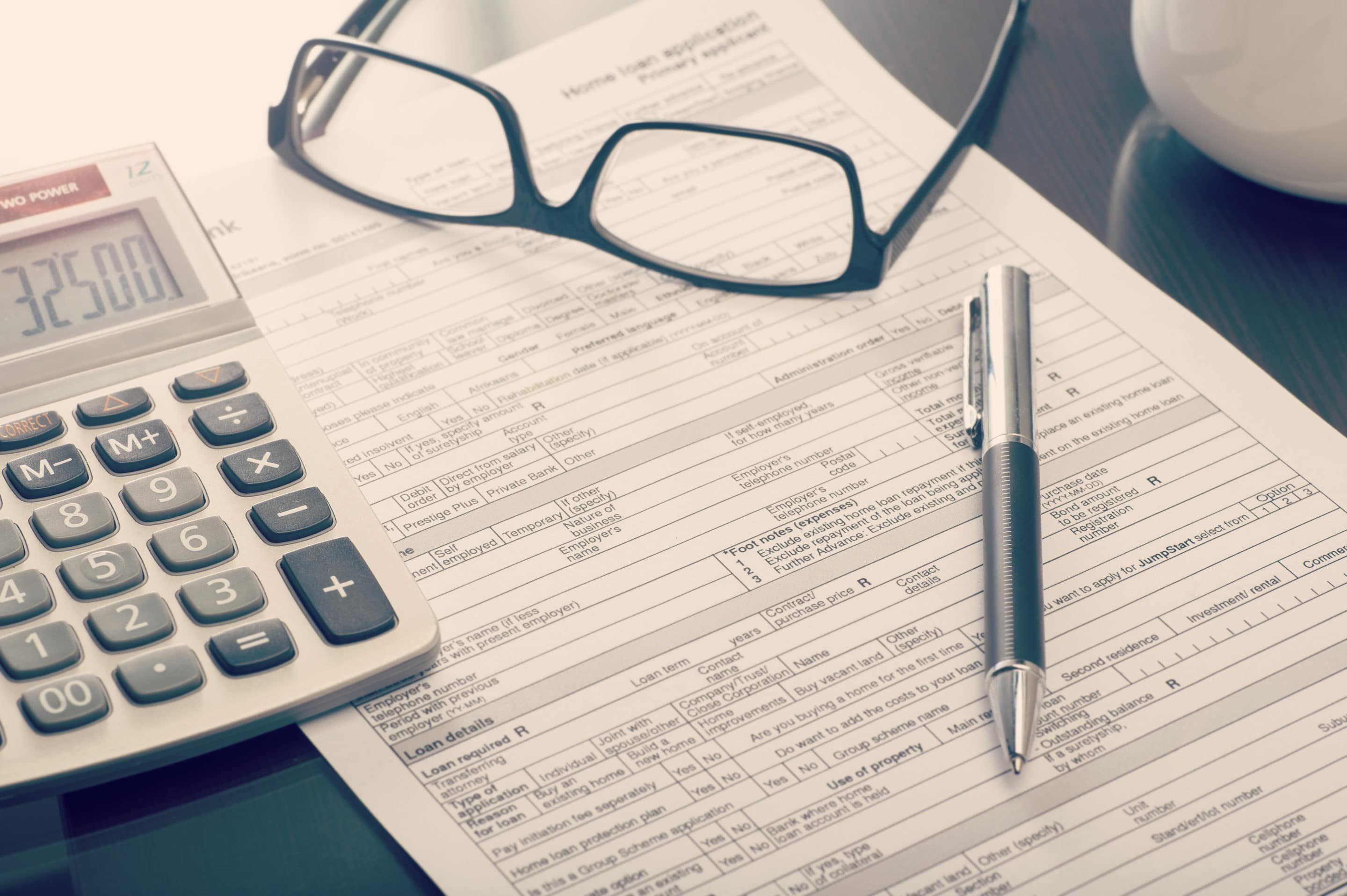 A commercial loan application on a table with a calculator, pen and glasses