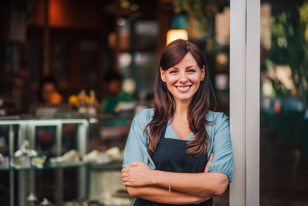 a smiling female business owner wearing an apron in front of her shop