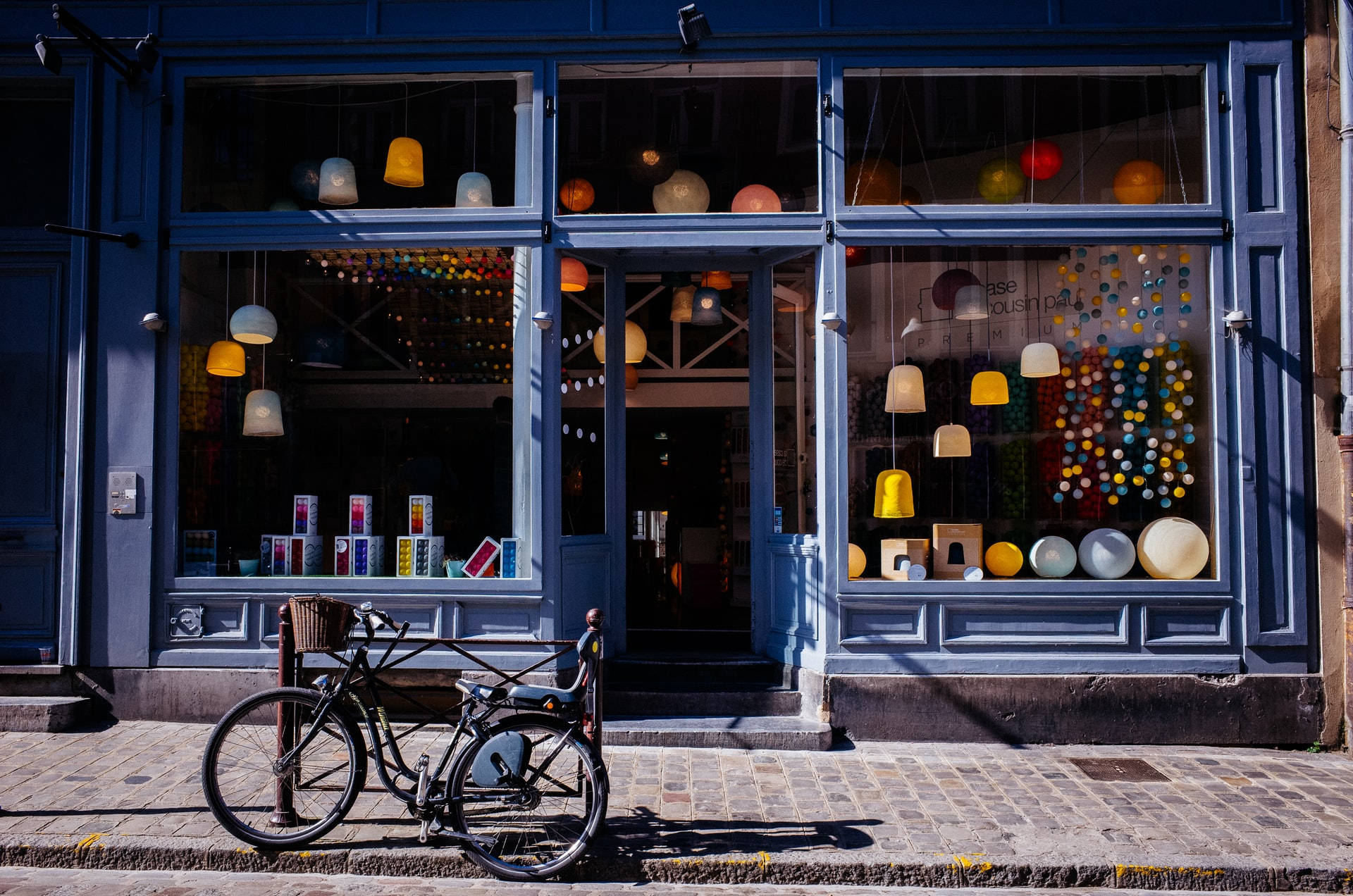a blue boutique storefront with a bike in front