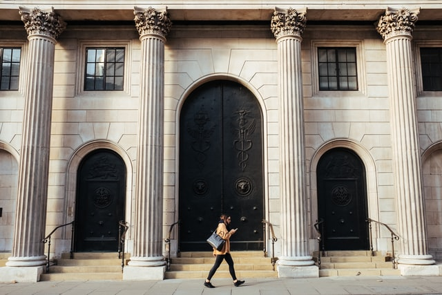 a person walking in front of a big old bank with pillars and a large door